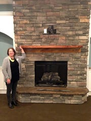 Lohman shows off the centerpiece fireplace in the large gathering room which greets residents as they walk through the front doors at BeeHive Homes.
