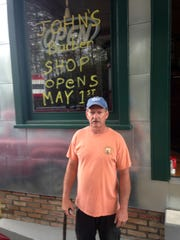 John York outside the window of the barber shop with a note about the reopening set for May 1.