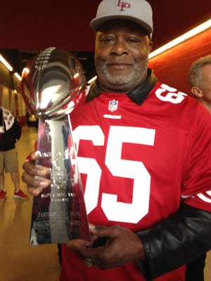 Alcorn State and NFL great Lawrence Pillers holds up the Lombardi Trophy.