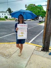 Lisa McCoy, a Northern Lebanon School District parent, combats the rain as she protests against district administrators who passed around a sex toy on May 10.