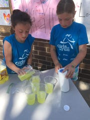 Third-graders Presley Goodrich of Johnston and Evelyn Meyer of Des Moines pour lemonade. Wallace Elementary's Girls on the Run club organized a lemonade fundraiser and run on May 17, 2018, for Kyle Tome, a fifth-grader who is fighting cancer.