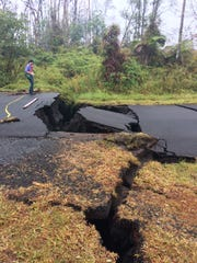 A geologist examines cracks in a road in the lower East Rift Zone of Kīlauea Volcano, Hawaii.