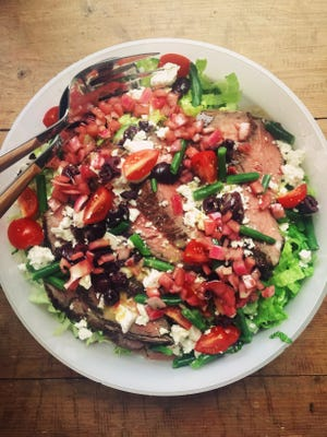 A meal-size Greek salad with flank steak.