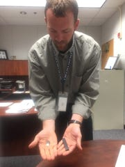 Granville High School Principal Matt Durst displays a confiscated JUUL e-cigarette device and flavored nicotine pod.