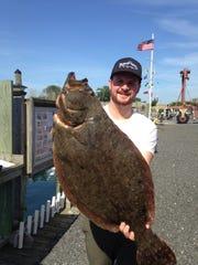 Kevin Newberg of Avon holds the 13-pound, 3-ounce fluke