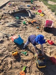 It's playtime in the dinosaur-themed sandbox at Jack's Place playground in Penfield's Rothfuss Park.