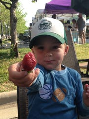 A child enjoys a strawberry at a local tailgate market