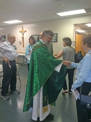 Rev. Richard Armstrong greets people after his first Mass at St. Therese Catholic Church in Clinton on July 1.