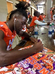 Clemson wide receiver Deon Cain puts his signature on a poster during the Tigers' 2017 Fan Day at Memorial Stadium.