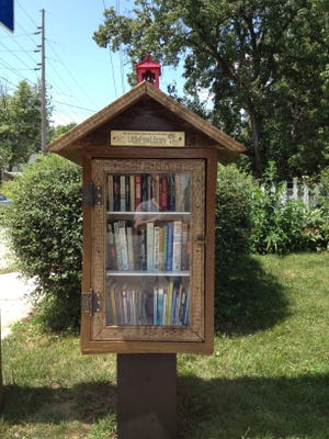 Thom Woodard rebuilt the Little Free Library outside his house at 40th and Illinois streets after vandals destroyed it.