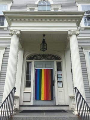 A Philadelphia pride flag hangs outside the Old Ship Church parish house on Main Street in Hingham. Selectmen declined to fly a pride flag outside of town hall this June, while the school committee voted to fly one at every Hingham Public School. Audrey Cooney/Wicked Local photo.