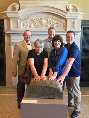 The large piece of Plymouth Rock on display at Pilgrim Hall has been touched by many hands over the last few decades, including a group of scholars who lectured here last fall. Above, genealogists Sue Allan, Caleb Johnson and Simon Neal pose with Pilgrim Hall President Don Brown, left, and Executive Director Donna Curtin, fourth from left, at the Rock.