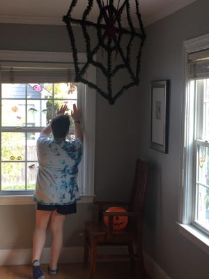 Daria Cohen's daughter, Molly, places decorations on the window.