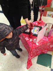 3-year-old Ethan helps put balloons on the display table at the Learning Experience in Freehold on Monday.