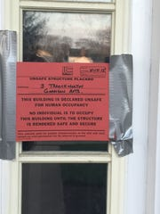 A red palcard posted by the Borough of Eatontown informs tenants that the Garrison Apartments are uninhabitable.