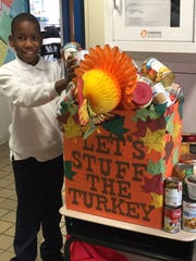 Linden School No. 4 students and staff members donated more than 200 non-perishable food items for a food drive sponsored by the school's PTA for the Linden Interfaith LINCS. Pictured is Tifuquan Lawrence adding to the donations on Nov. 20.