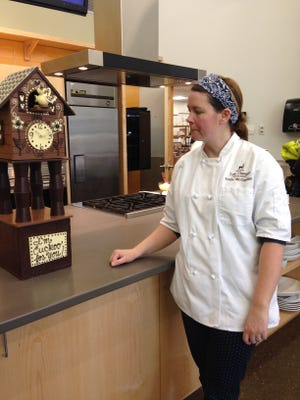 Emily McCracken with a smaller model of a five-foot cuckoo clock she sculpted that will be featured on the Food Network.