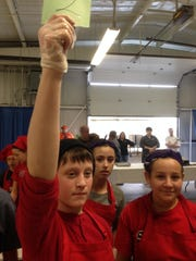 Sharon Elementary School sixth-grader Tom Bissaillon holds up a green card to indicate his team is finished Saturday at the Junior Iron Chef competition at the Champlain Valley Expo. His teammate Macy DeMara stands to his right.