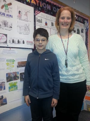 Ethan Beatty with fifth grade teacher Lisa Reynolds in front of Ethan's Bill of Rights in Action project.