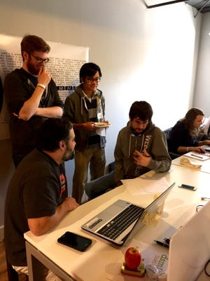 A team of developers debate a project during the 2015 Des Moines Charity Hackathon at Gravitate Thursday, Feb. 26, 2015. The hackathon is helping 10 Des Moines nonprofits redesign websites, build databases and develop other web tools.