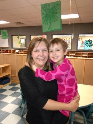 Loni Jorgenson of Mason City holds her son, Talon, who prefers wearing girls' clothing. He plays in the photo, below.