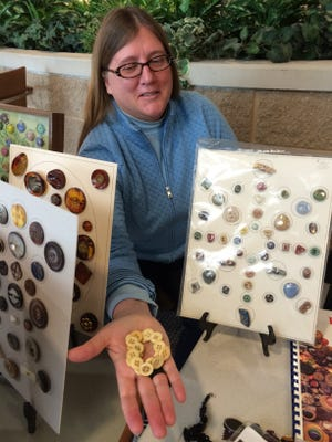 Button collector Gwen Biddle of Winneconne holds a string of old underwear (union suit) buttons. They were made of bone during the 17th and 18th centuries, soaked or steamed to soften and then separated into sheets. A circular saw was used to cut out the button blanks.
