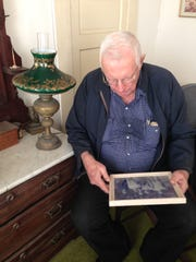 Jim English looks at a family photo in the Alva house where he and his father were born.