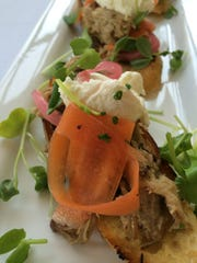 Braised pork shoulder tartine topped with cilantro, radish, pickled onion, carrot and farmers cheese over three toasted pieces of French bread.