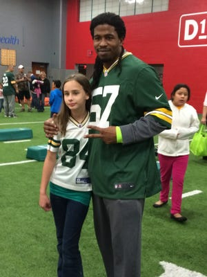 "Green Bay Packers linebacker Jamari Lattimore poses with a young fan during a PALS program fitness event at Bellin Health's Perfomance Center on Monday, Oct. 20, 2014. The PALS program connects adult ""pals"" with kids from low-income families."