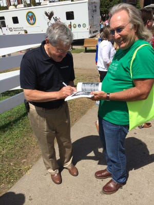 Iowa Gov. Terry Branstad signs an autograph before his speech on the Des Moines Register Political Soapbox at the Iowa State Fair.