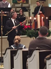 Dr. Don Thrasher lights the Advent candle during the Christmas cantata on Sunday at Northside United Methodist Church in Jackson.