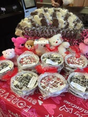 Kathy's Kandies has a table of assorted chocolate, stuffed animals, suckers and chocolate pizzas for Valentine's Day.