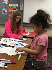 Tapanga Smith, right, spent the evening coloring, while her mother attended a bornlearning workshop on routines and learning on the go. Kaleigh Marchand, a student at Ivy Tech Community College, volunteered to watch children during the event.