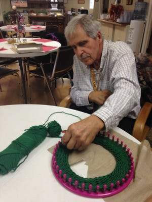 George Doxtader, 67, knits using a loom at the Eaton Rapids Senior Center. After two massive strokes he has taken up the hobby with the help of volunteers there.