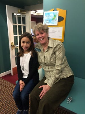 Claire Abdou, 9, a fourth-grader at Our Lady of Good Counsel, visits with library staffer Susan Stoney at the Winter Festival.