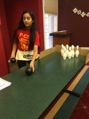 Palak Patel, 16, a Plymouth High School junior, volunteers at the tabletop bowling game during the Winter Festival. Patel was among National Honor Society volunteers from Plymouth-Canton Educational Park.