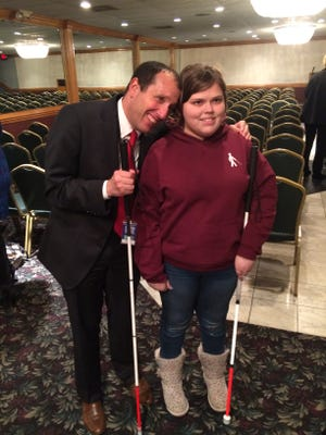 Michigan Supreme Court Justice Richard Bernstein poses for a photo with Brianna Costigan, 16, following Bernstein's speech about overcoming adversity.
