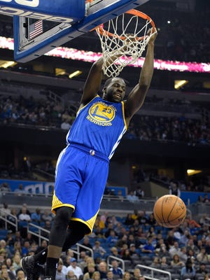 Golden State forward Draymond Green (23) hangs on the rim after dunking the ball during the first half Wednesday.