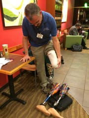 Dave Dunville demonstrates how he puts on his prosthetic