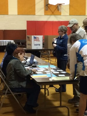 Voters fill out voter applications this morning at First Christian Church in Lansing Township.