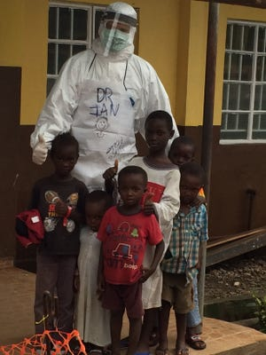 Dr. Ian Crozier stands with children he treated for Ebola.