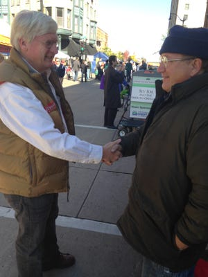 Glenn Grothman shakes hands with a man while campaigning at the Oshkosh farmers market.