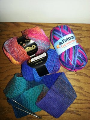 Balls of yarn, knitting needles and a scarf.