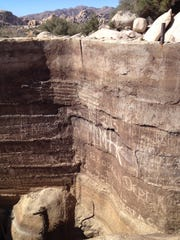 Graffiti has been etched into the concrete of Barker Dam in recent years at Joshua Tree National Park. Researchers from the University of New Mexico and the University of Vermont are assisting the park in an effort to remove the graffiti using a technique that involves dabbing acrylic paint onto patches that have been vandalized.