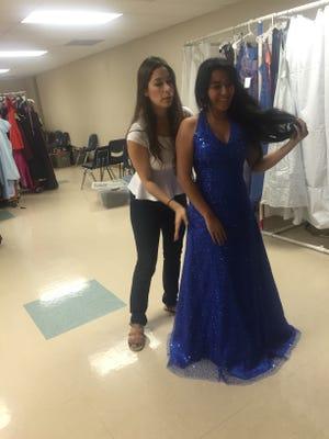 Volunteer Tamara Canedo helps Selena Gomez pick out a prom dress Saturday in Coachella at the Bagdouma Park Community Center.