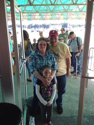 Jeannette Colvert with Terry Madden and his daughter, Gracie Madden, 9, are the first to enter the 2014 Pensacola Interstate Fair grand opening on Thursday afternoon.