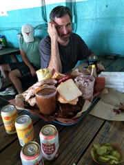 Chef Kevin Binkley ponders the overflowing tray of food at Franklin Barbecue, an Austin restaurant that follows time-honored Texas cooking methods and portions.