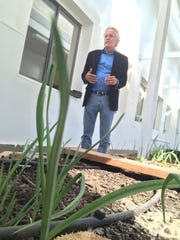 STAR School Co founder and director Dr. Mark Sorensen stands in a greenhouse with vegetables produced by students.