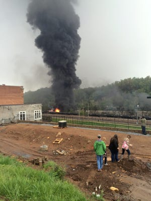 In this mobile phone photo provided Charles Peters, people look on as smoke rises after several CSX tanker cars carrying crude oil derailed on Wednesday in Lynchburg, Va. Authorities evacuated numerous buildings Wednesday after the derailment.