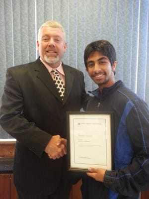Dr. Dwight Bonk, principal of John Jay High School, is pictured with Rajat S. Chandra, winner of a National Merit $2,500 scholarship.